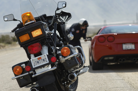 traffic cop: Traffic cop talking with sports car driver, focus on motorcycle in foreground