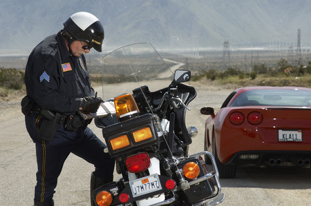 Traffic cop writing against motorcycle on country road