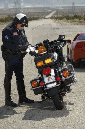 traffic ticket: Traffic cop writing against motorcycle on country road