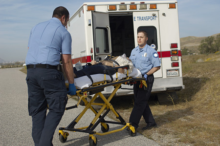 transporting: Paramedics transporting victim on stretcher
