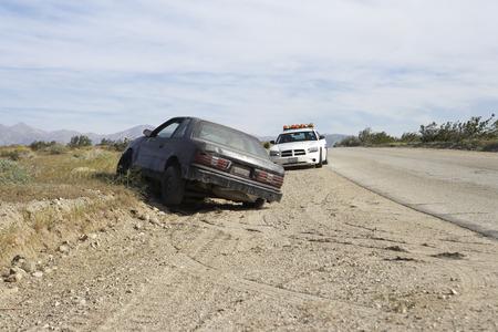 abandoned car: Coche de polic�a cerca de coches abandonados en la carretera LANG_EVOIMAGES