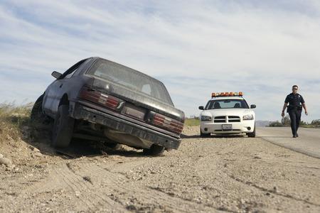 abandoned car: Agente de la polic�a caminando hacia el coche abandonado en carretera LANG_EVOIMAGES