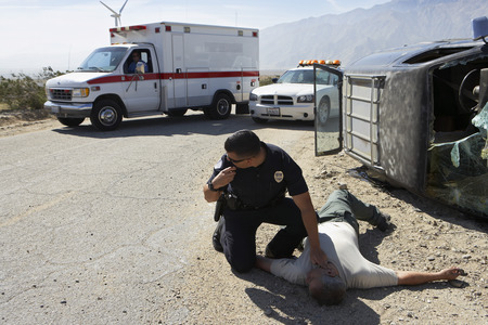Policeman checking pulse of car crash victim