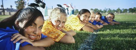 Teenage girls (13-16) lying in row on soccer field Stock Photo - 3906418