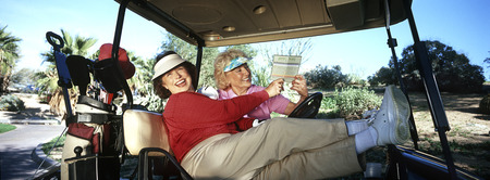 Two senior women laughing in golf cart Stock Photo - 3906380
