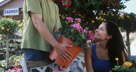 garden center: Man showing plant to woman in garden center LANG_EVOIMAGES