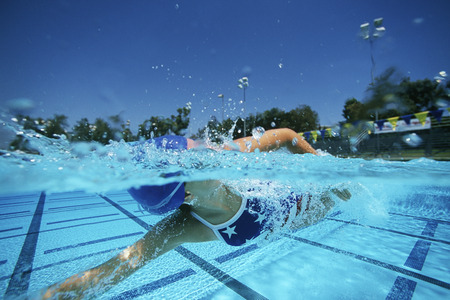 backstroke: Female swimmer in pool, surface view LANG_EVOIMAGES