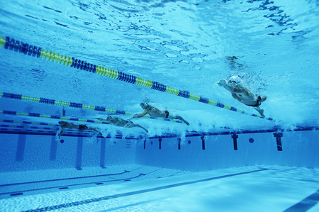 Male swimmers racing in pool, underwater view LANG_EVOIMAGES