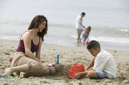 Mother building sandcastles with son on beach Stock Photo - 4926042