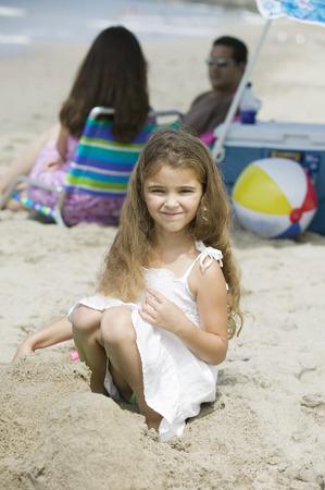 squatting: Retrato de ni�a en la playa, los padres en el fondo