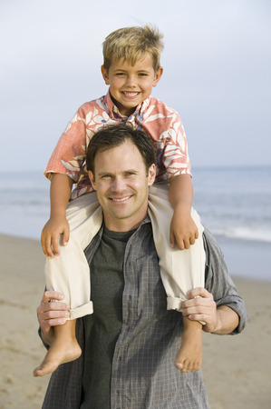 Portrait of boy on fathers shoulders at beach Stock Photo - 4926024