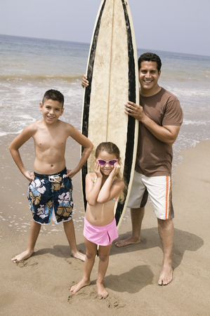 Portrait of man holding surfboard with children on beach  Stock Photo - 4926100