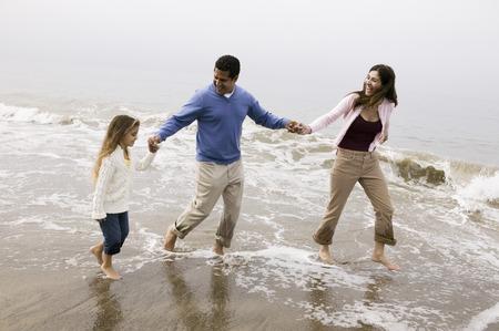 Family walking through surf on beach Stock Photo - 4926085