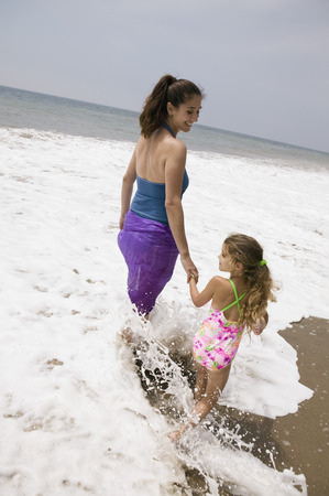 Mother and daughter walking through surf Stock Photo - 4926019