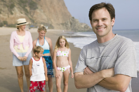 Portrait of man on beach with family Stock Photo - 4926047