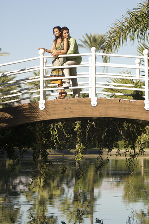 Couple embracing on bridge in park Stock Photo - 4926095