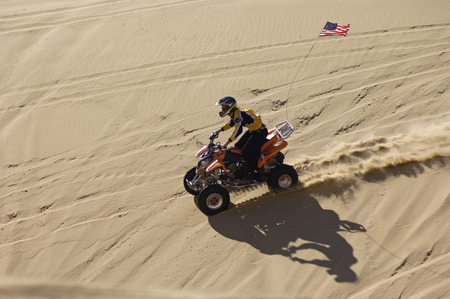 four year olds: Young Man Riding ATV Over Sand Dune