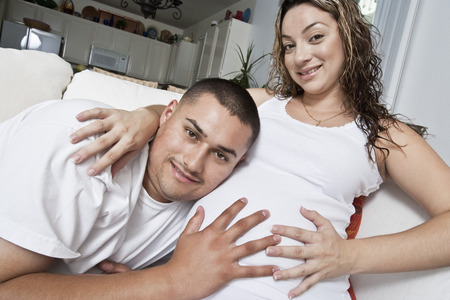 Portrait of expectant couple touching belly Stock Photo - 4926075