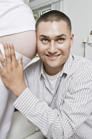 Smiling man with head at pregnant woman's abdomen Stock Photo - 4926097