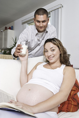 pregnant relaxing on sofa: Portrait of expectant couple, man serving glass of milk to woman