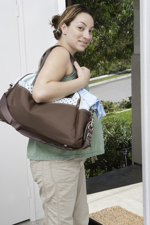 Pregnant woman exiting house Stock Photo - 4926048
