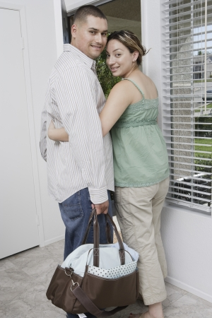 Expectant couple exiting house Stock Photo - 4926060