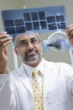 middle easterners: Dentist looking at x-ray LANG_EVOIMAGES