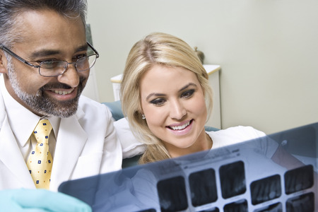 Dentist and patient looking at x-ray Stock Photo - 4926023