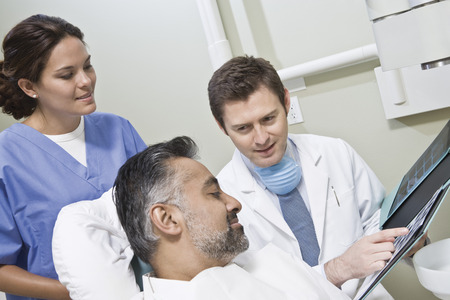 Dentist and patient looking at x-ray Stock Photo - 4926030