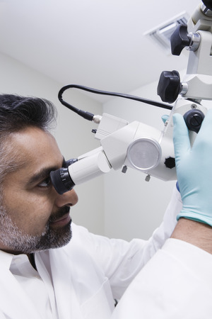 middle easterners: Doctor using microscope LANG_EVOIMAGES