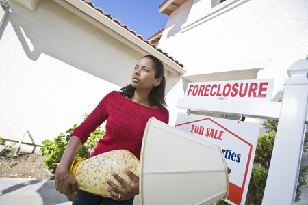 foreclosure: Sad mid adult woman moving out of house LANG_EVOIMAGES