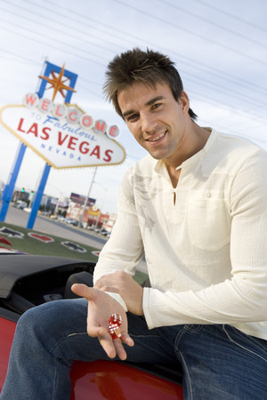 Man holding dice, Las Vegas 'welcome' sign in background  Stock Photo - 4926135