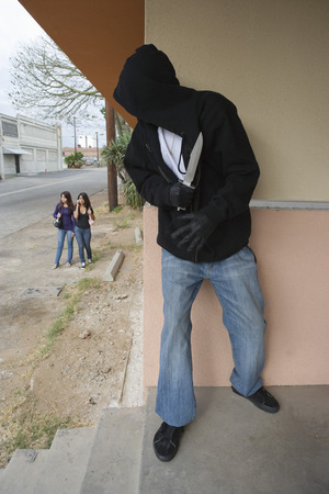 Robber with knife hiding behind corner and waiting for two girls Stock Photo - 4926160