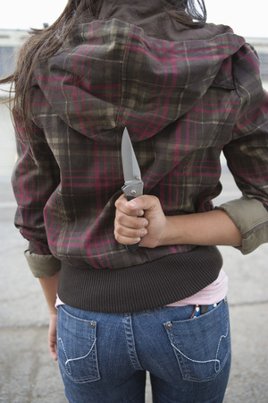 Young woman holding knife behind back Stock Photo - 4926158