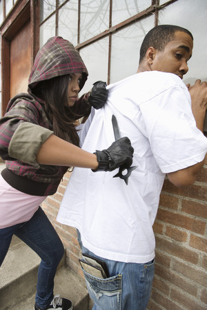 Young woman robbing man with knife Stock Photo - 4926154
