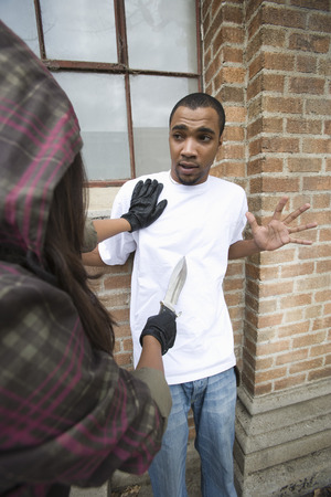robbing: Young woman robbing man with knife