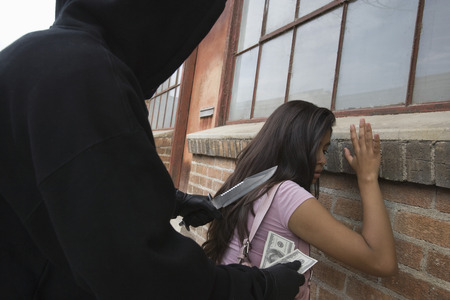 Hooded man robbing young woman with knife Stock Photo - 4926152