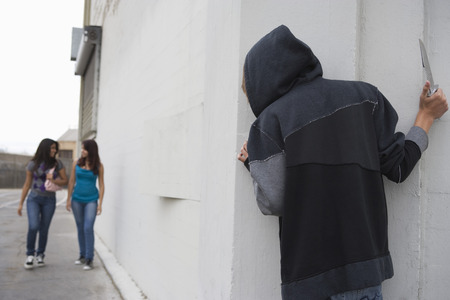Robber with knife hiding behind corner and waiting for two girls Stock Photo - 4926138