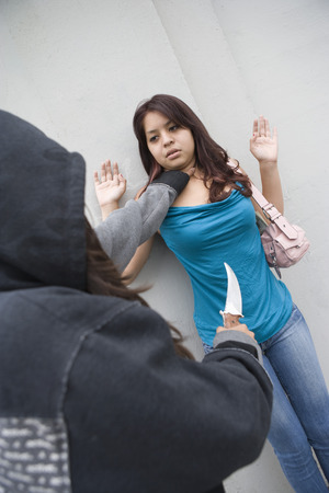 Hooded woman robbing young woman with knife Stock Photo - 4926148