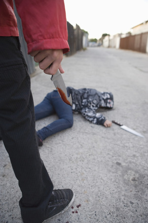 Man standing next to stabbed man lying on ground Stock Photo - 4926146