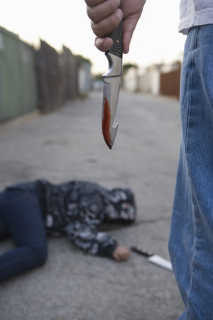 Man standing next to stabbed man lying on ground Stock Photo - 4926144
