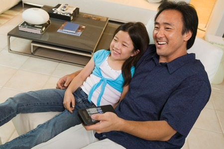 decisionmaking: Father and Daughter Watching TV Together LANG_EVOIMAGES
