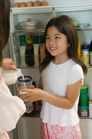 Mother Pouring Milk For Daughter Stock Photo - 5404639