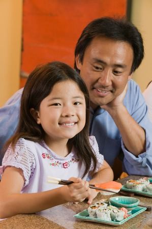 early 30s: Father Watching Daughter Eat Sushi