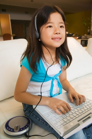Girl Using Laptop and Listening to Music Stock Photo - 5404646