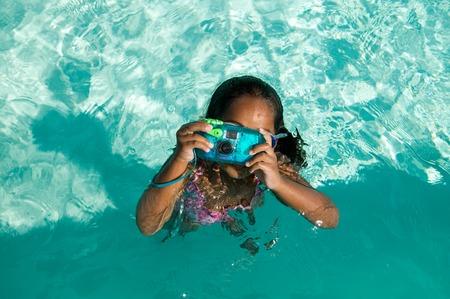 Girl Using Waterproof Camera in Swimming Pool Stock Photo - 5404689