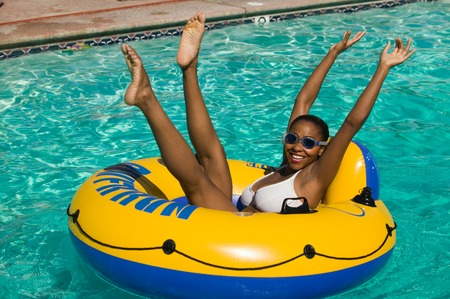summertime: Woman Raising Arms and Legs in Pool Float LANG_EVOIMAGES