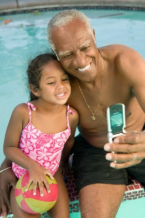 Grandfather and Granddaugther Posing for Camera Phone Stock Photo - 5404702