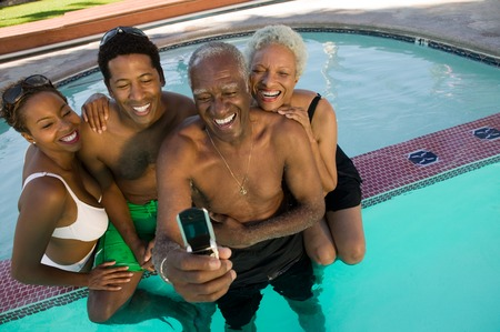 Family Posing for Camera Phone Picture in Pool Stock Photo - 5404704