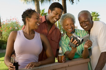 early 30s: Family Looking at Video Camera at Barbecue